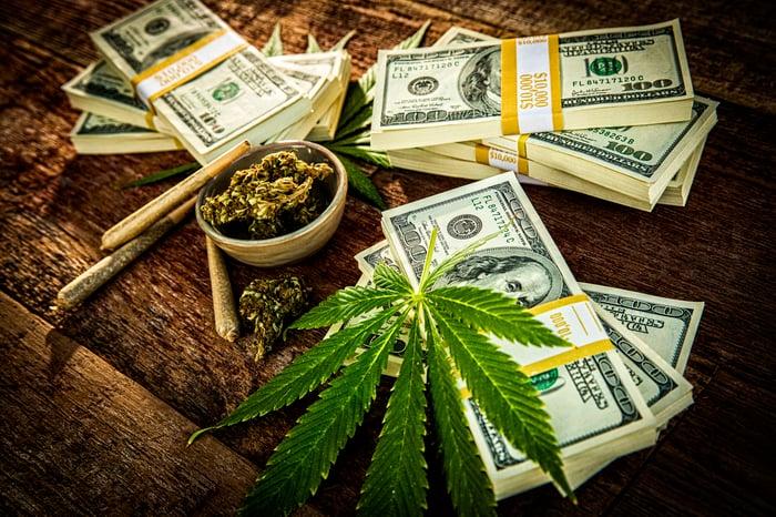 Cannabis flower buds, joint, marijauana leaf and bundles of American dollar bills.