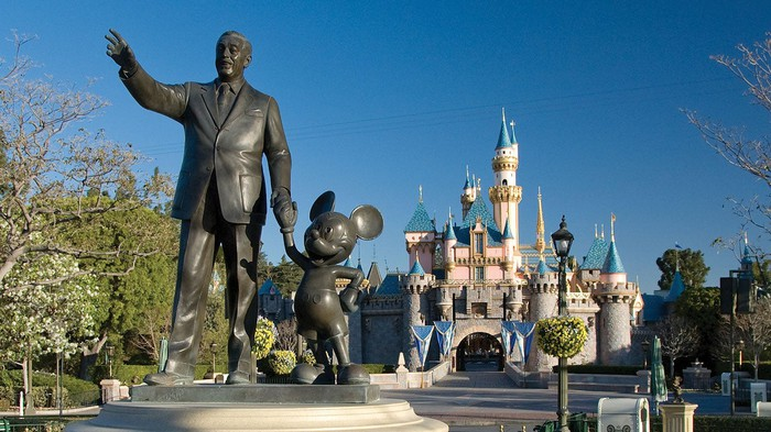 A Walt Disney and Mickey Mouse statue in front of Disneyland's signature castle.
