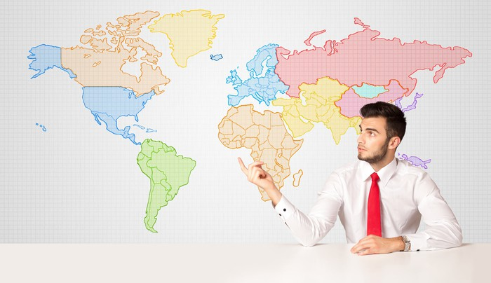 A young man in a red tie points to a large world map on the wall behind him.