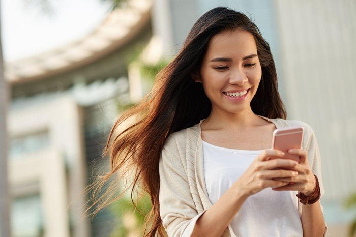 Woman engaging with mobile phone.
