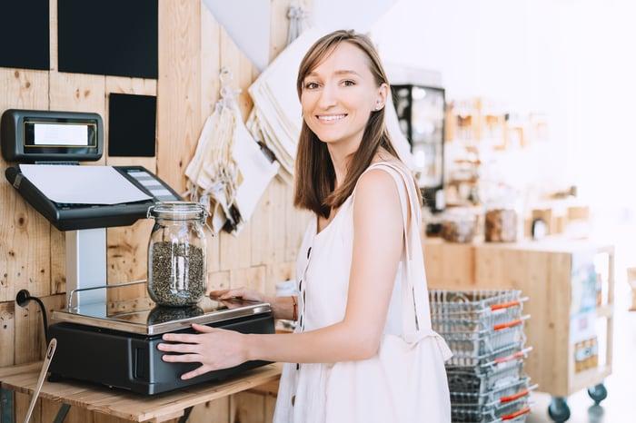 Woman weighing hemp seeds at a dispensary.