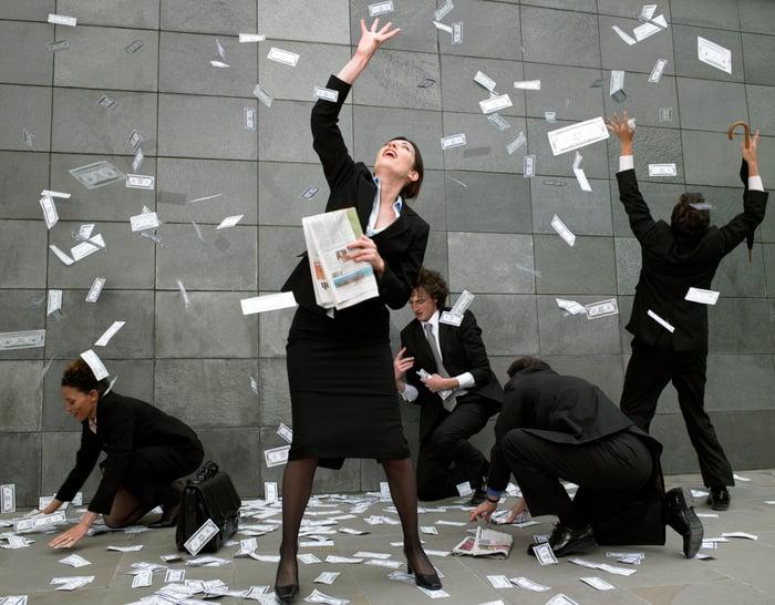Les gens attrapent des billets d'un dollar tombant du ciel à l'extérieur d'un bâtiment de la ville.