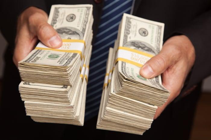 A businessman holding two gigantic stacks of one hundred dollar bills.