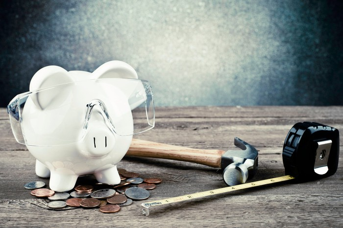 A piggy bank with safety goggles on surrounded by a hammer, a tape measure, and loose change.