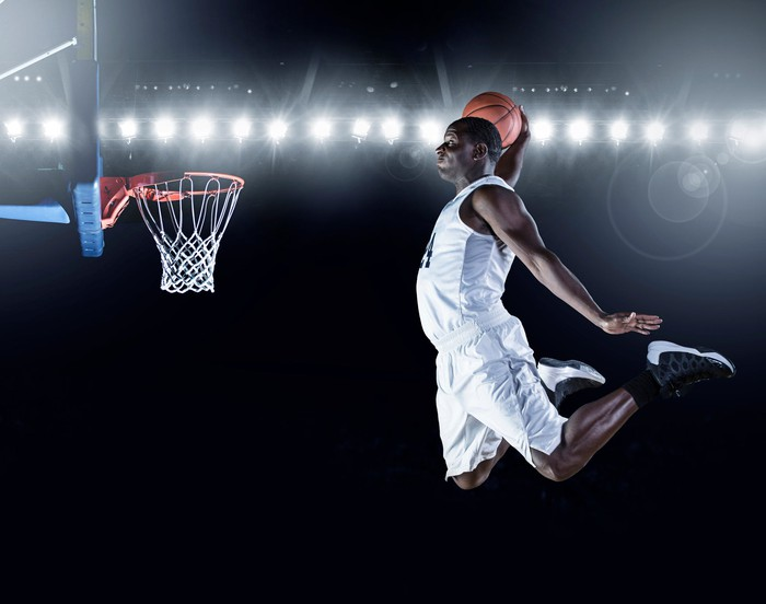 Basketball player leaping to slam dunk a ball
