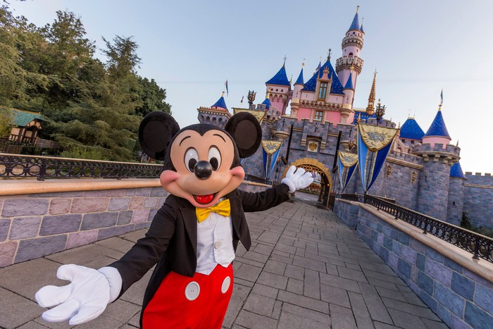 Mickey Mouse stands in front of the Sleeping Beauty Castle to welcome fans back to Disneyland.