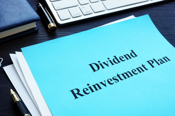 Laptop and papers that say Dividend Reinvestment Plan on desk