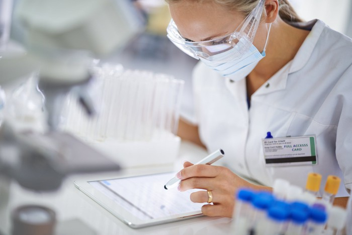 A masked woman in a lab setting reviews information on a tablet.