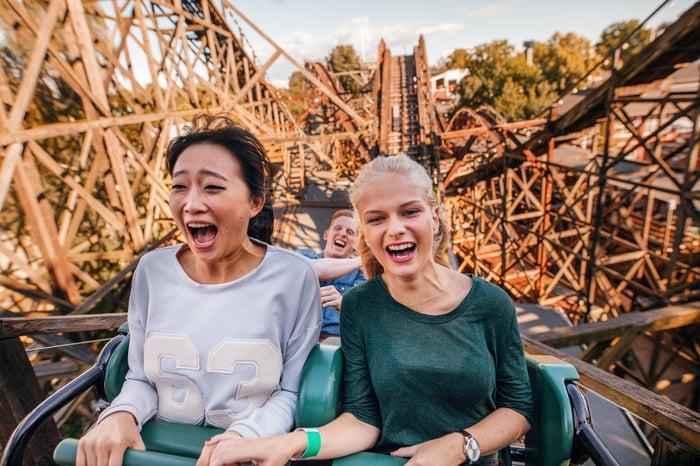 Two women on wooden roller coaster ascending.