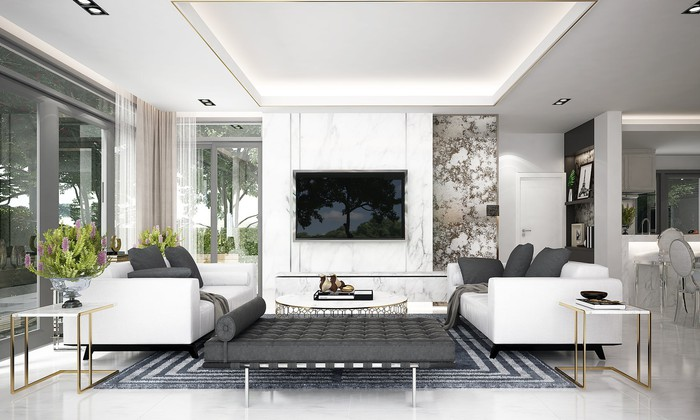 Living room with couches, table, and big TV, with lots of windows and white walls.