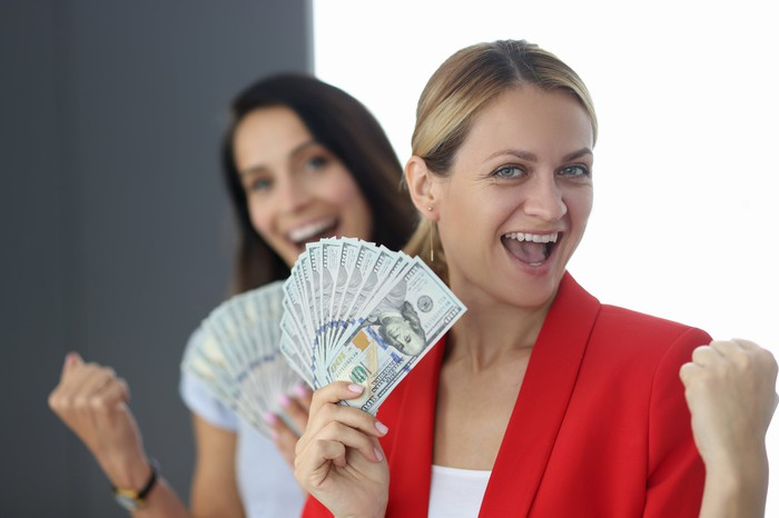 Two women triumphantly holding fanned out cash.
