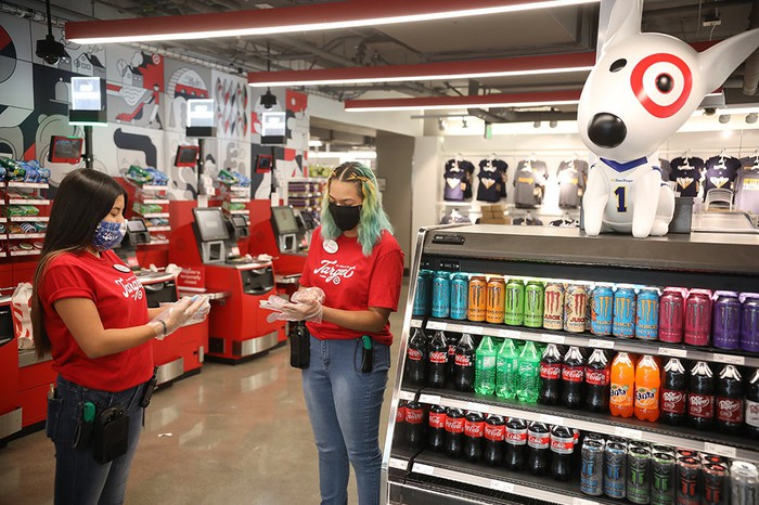 Two Target employees put on personal protective equipment in the checkout section of a Target store