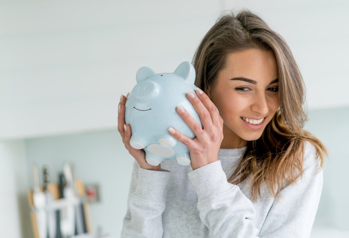 A young woman holds a piggy bank up to her ear.