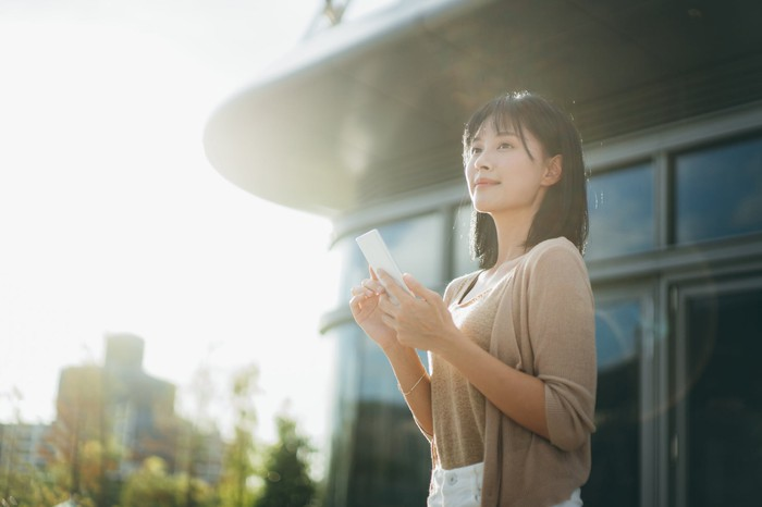 Happy young woman standing outdoors with mobile phone in hand.
