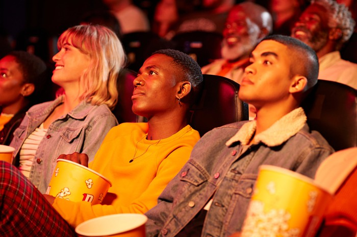 People in theater with popcorn buckets