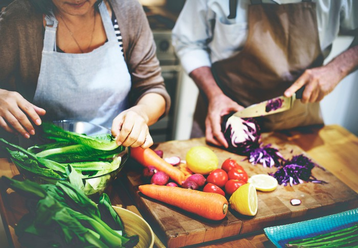 Two people prepare vegetables in a kitchen.