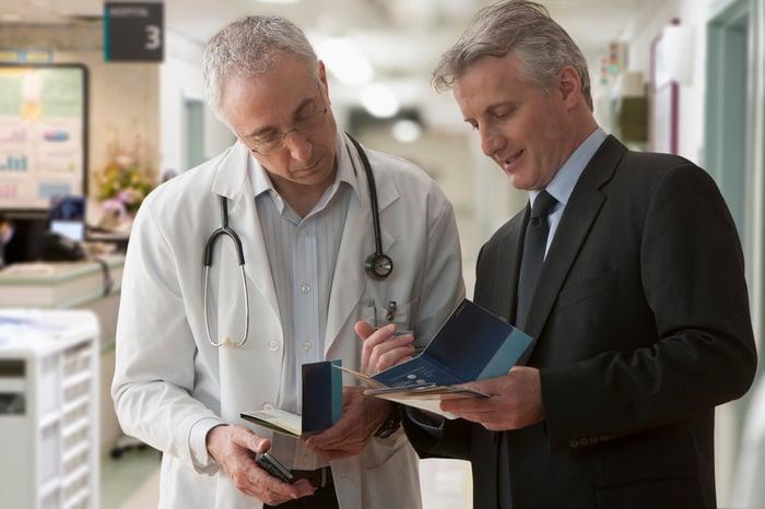 Un médecin et un homme en costume discutent d'une brochure d'information.