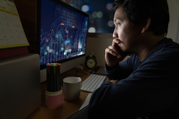 A trader considers a stock chart in a dark room.