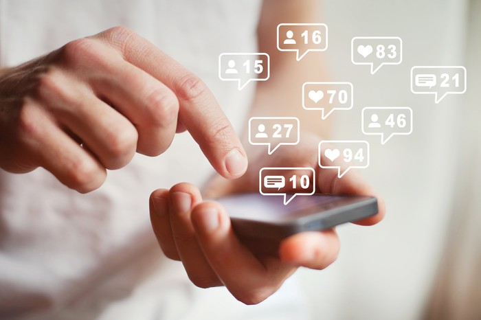 Smartphone in hand with finger pressing it, and social media metrics above.