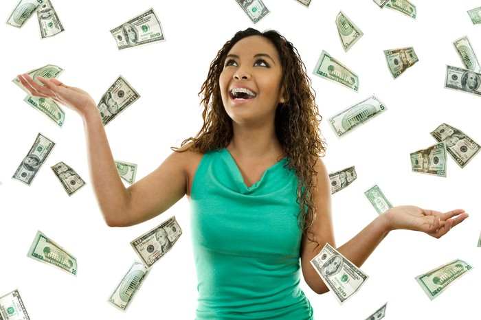 A smiling young woman is grabbing hundred-dollar bills floating in the air around her.