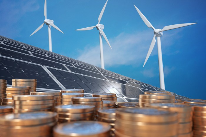 Stacks of coins with wind turbines and solar panels in the background.