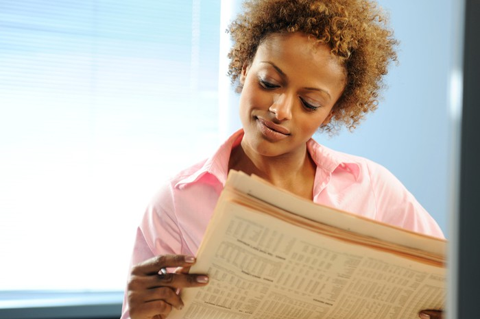 A businesswoman reading a financial newspaper with visible stock quotes.