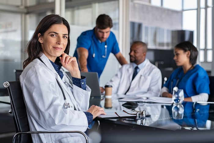 A team of healthcare professionals is gathered around a table in a conference room.