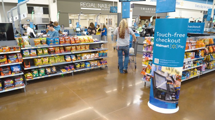A customer pushes a cart through the aisles of a walmart store with a sign promoting touch-free checkout.