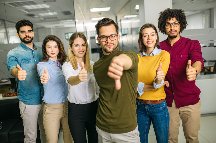 A group of millennials with thumbs up and thumbs down.