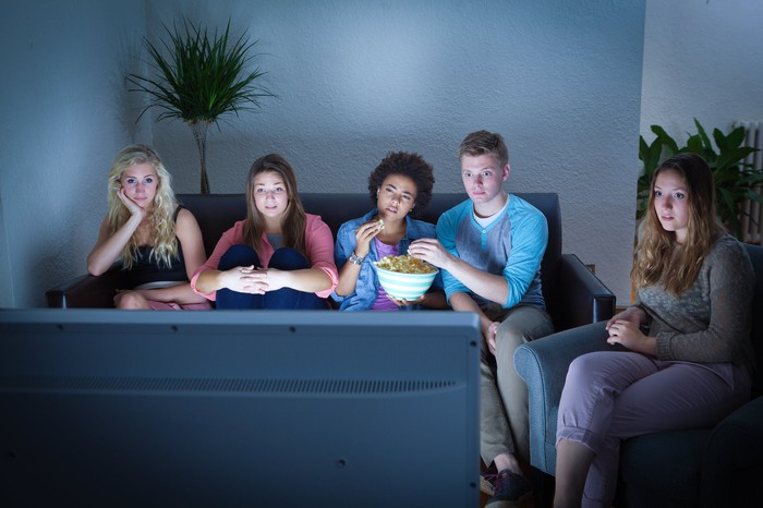Group of teenagers watching TV while eating popcorn.