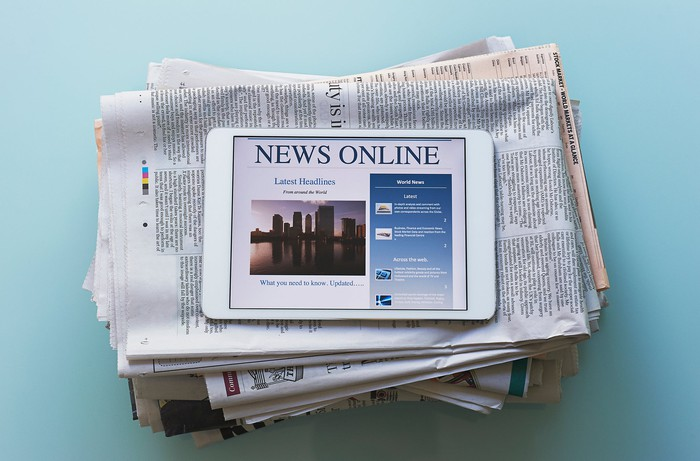 Tablet with news online sitting on stack of newspapers