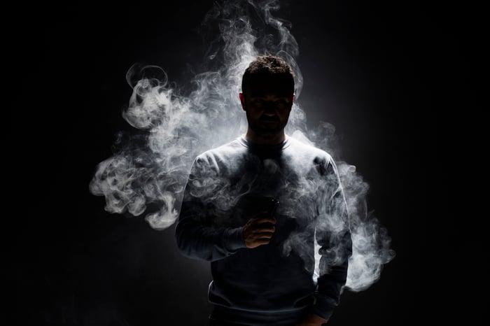 Person smoking an e-cig in a dark room.