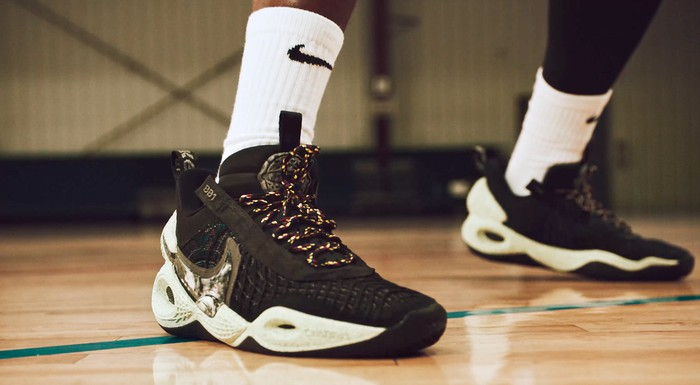 A basketball player's feet clad with Nike branded shoes and socks.