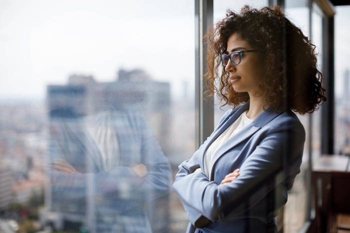 Woman wearing glasses and a suit looks out a window from a high rise.