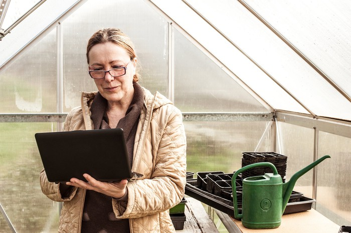 Mature woman with glasses on and holding a laptop.