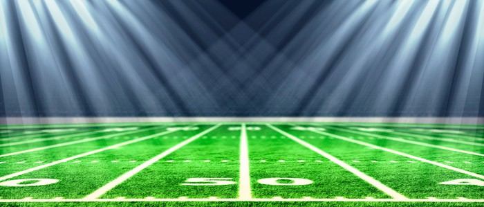 Lights are shining on the 50-yard line of a football field.