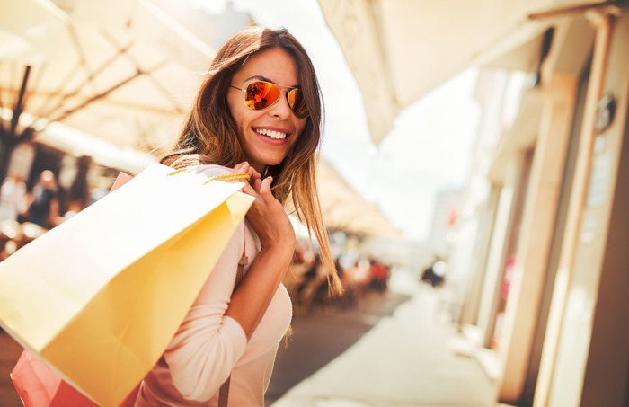 A smiling woman in sunglasses goes shopping.