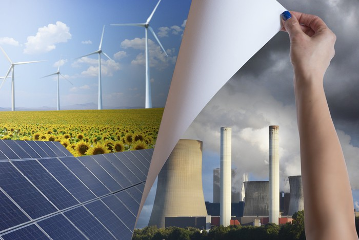 A hand replacing a poster of power station chimneys by one with wind mills and solar panels.