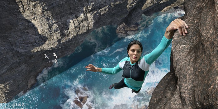 Woman hanging on the edge of a cliff with one hand above a rushing river.
