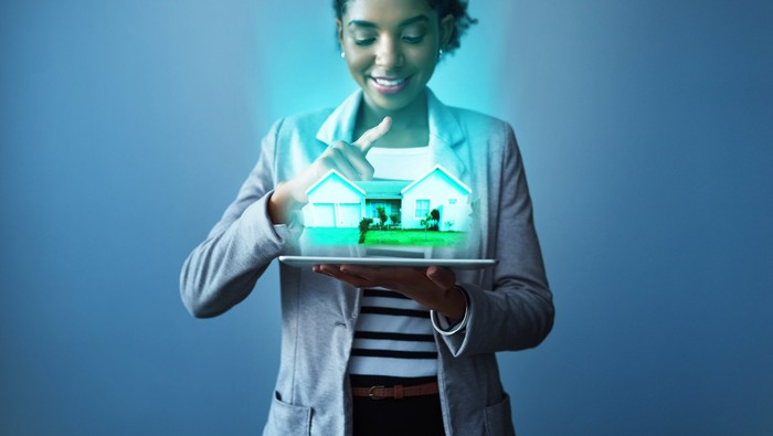 Real estate agent using tablet to show digital projection of a property