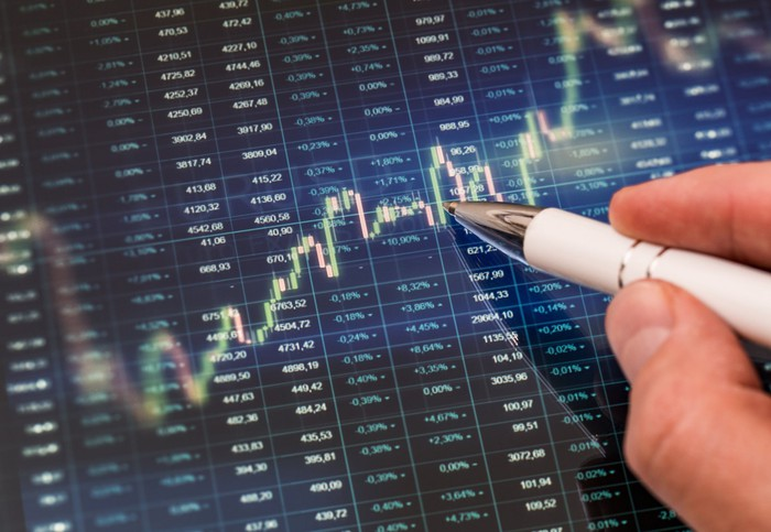 A hand holding a pen pointing to a candlestick chart with stock quotes in the background.