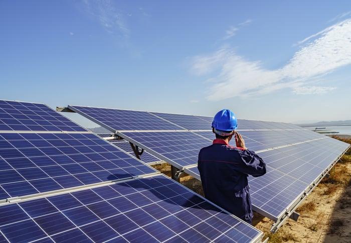 Un travailleur parle au téléphone tout en s'appuyant sur un panneau solaire.