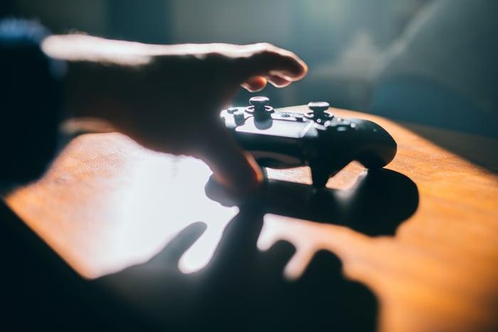 Une main tendue vers un contrôleur de jeu vidéo.