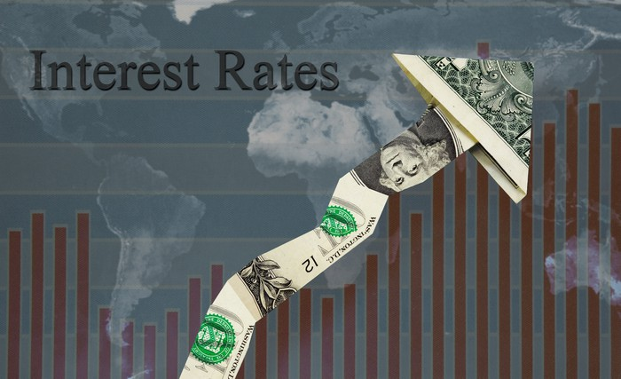 A rising line with an arrow made out of folded one dollar bills, with the word interest rates in the background.