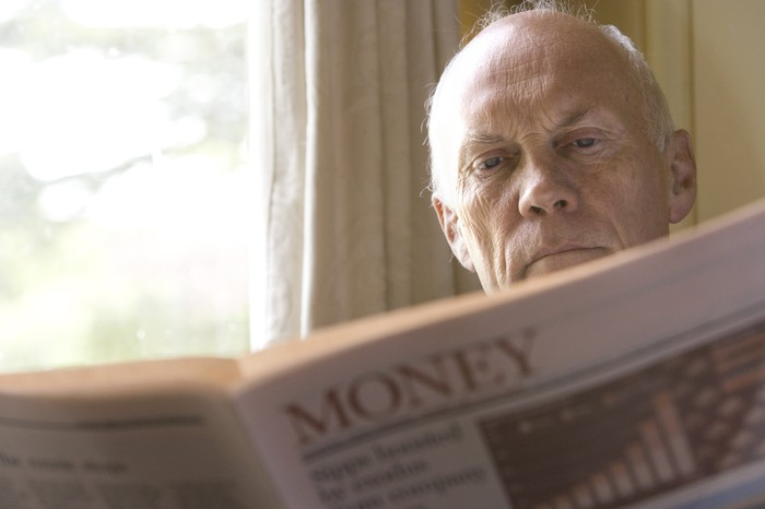 An elderly man reading the money section of a newspaper.