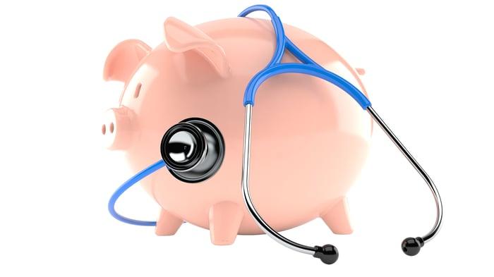 A piggy bank wearing a stethoscope.