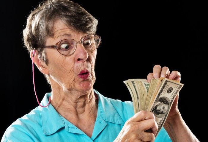 An older woman is counting her money, looking surprised.