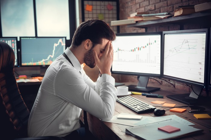 An upset investor massages his temples in front of a trading screen.