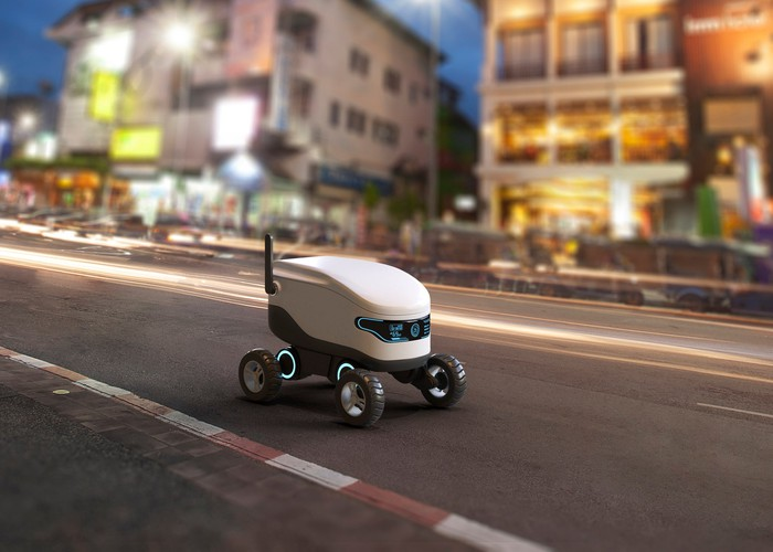 A delivery robot concept shown driving along a street outside lighted nighttime buildings.