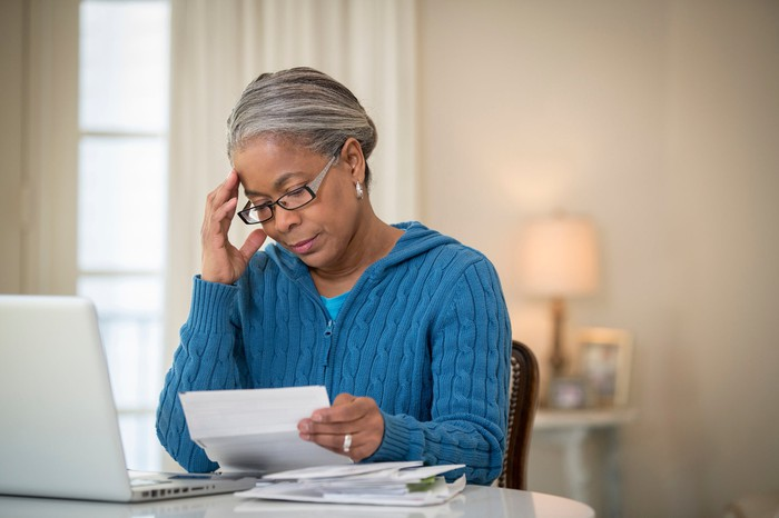 Senior woman wearing blue sweater sits in front of a laptop, glancing over bills.